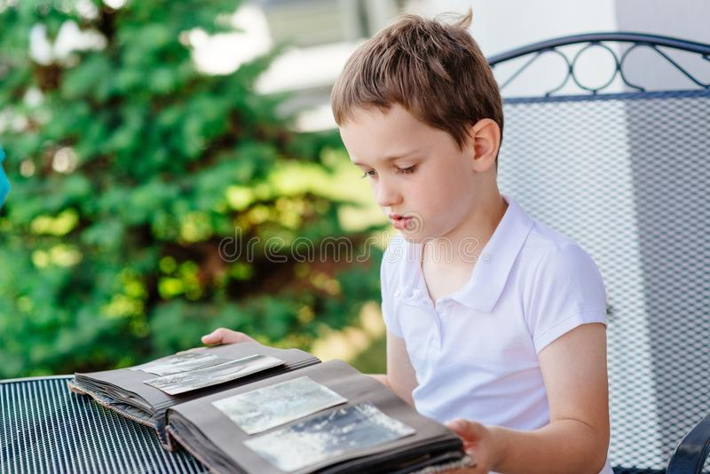 Weinig 7 jaar oude jongens die oud fotoalbum doorbladeren royalty-vrije stock afbeeldingen