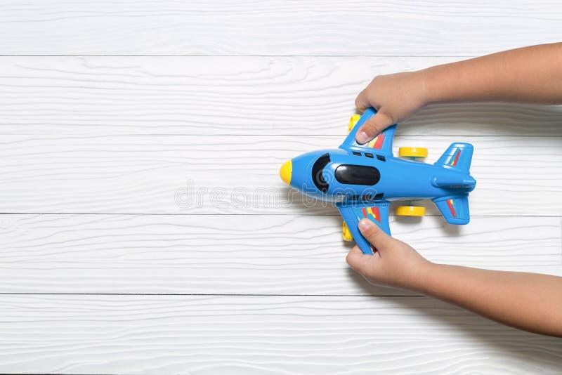 Weinig jong geitje dat blauw vliegtuigstuk speelgoed houdt Verbeeldingsconcept stock foto
