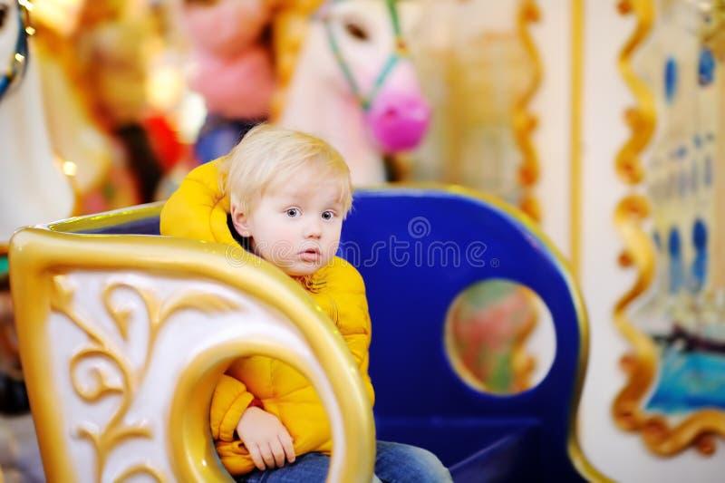 Weinig jong geitje die op kleurrijke vrolijke carrousel berijden gaat rond tijdens markt stock foto's