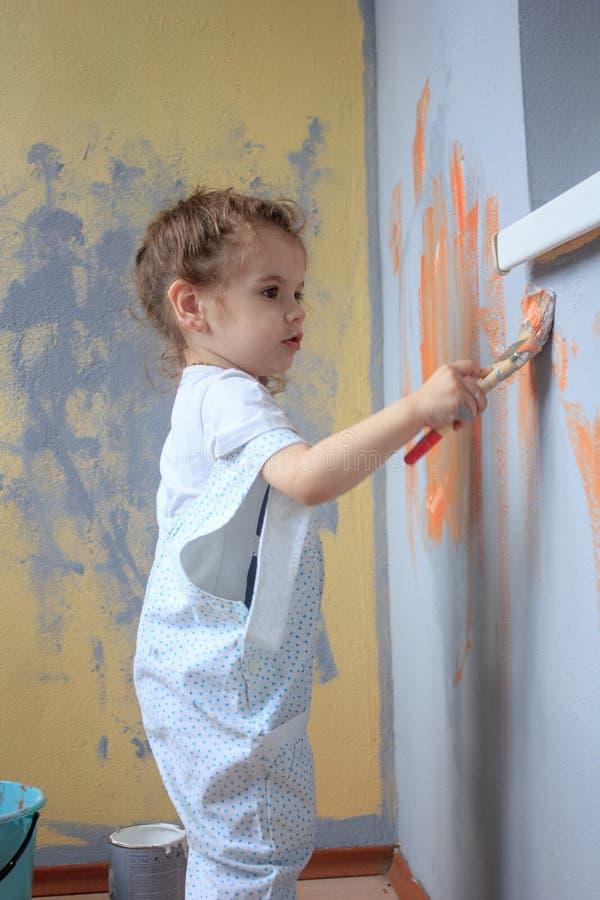 Weinig jong geitje die pret met verfborstel hebben, die vernieuwend muren door kleurenverven helpen stock foto