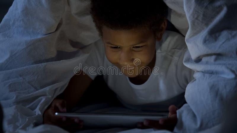 Weinig jong geitje die die tablet in het geheim bij nacht bekijken, met hoofd in deken wordt behandeld stock foto
