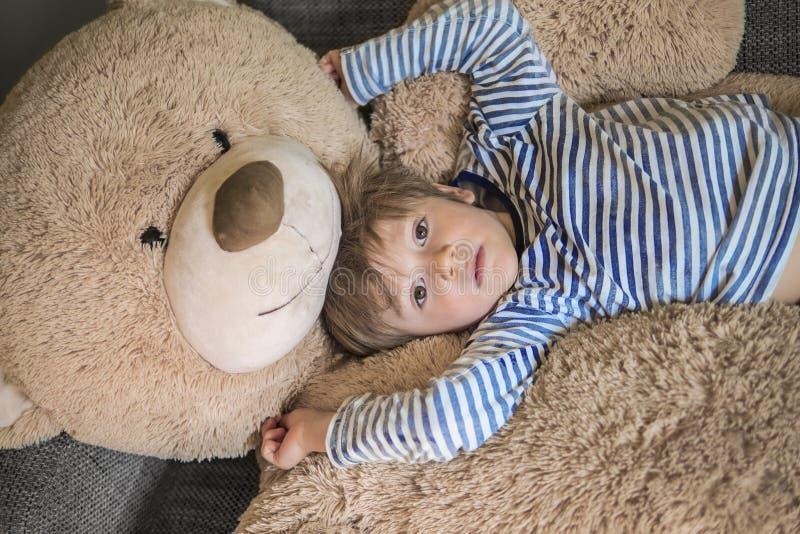 Weinig jong geitje die uit met zijn teddy hangen stock foto's