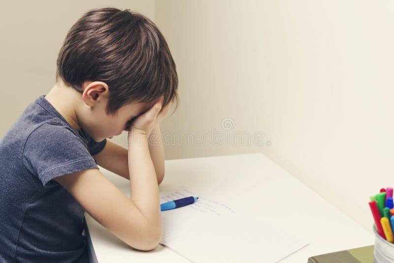 Weinig jong geitje maakte thuis zijn thuiswerk De jongen is vermoeid en behandelt zijn gezicht met handen stock afbeeldingen