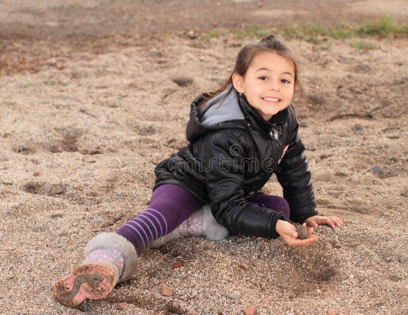 Weinig jong geitje - meisje het spelen in zand stock fotografie