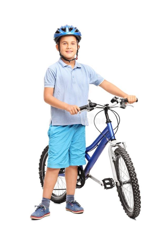 Weinig jong geitje met blauwhelm het stellen naast zijn fiets royalty-vrije stock afbeelding