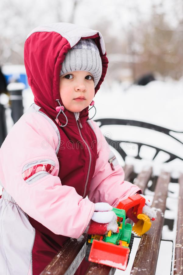 Weinig jong geitje speelt met speelgoed in de winter in het park royalty-vrije stock foto's
