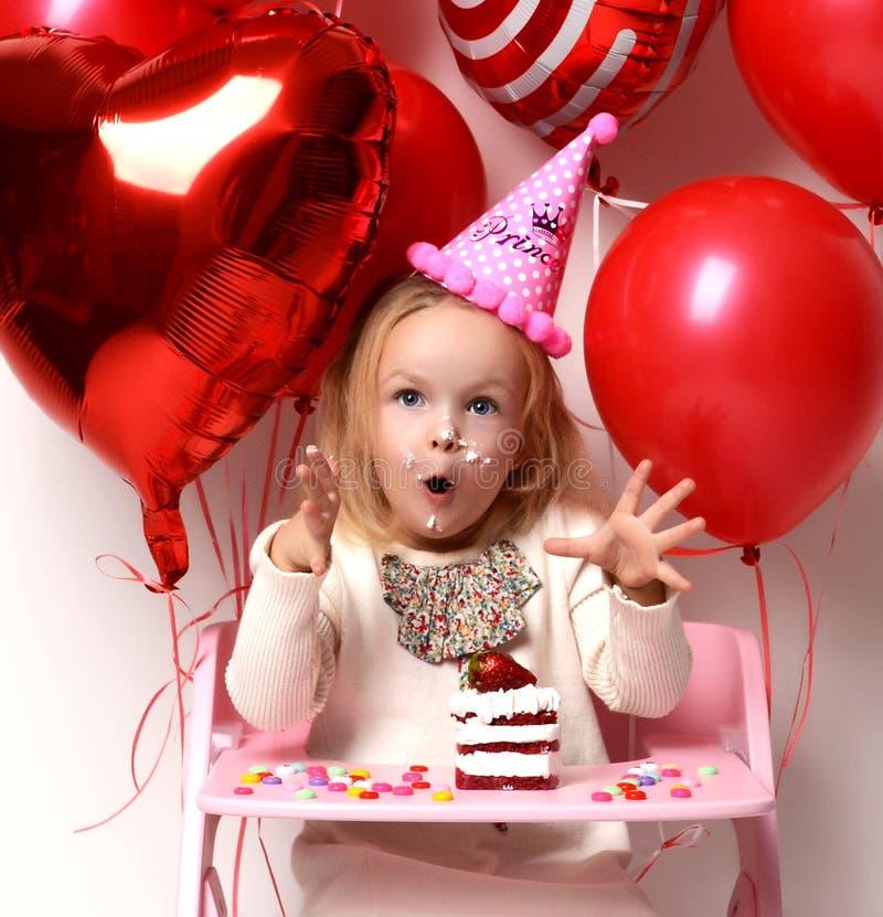 Weinig jong geitje van het babymeisje viert verjaardagspartij met zoete cake en suikergoed het gelukkige gillen stock fotografie