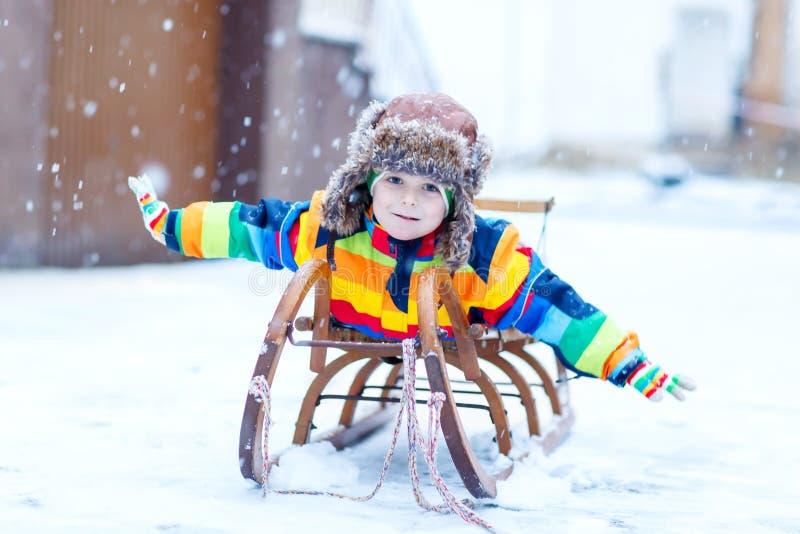 Weinig jong geitjejongen die ar van rit genieten tijdens sneeuwval Gelukkig peuterjong geitje die op uitstekende slee berijden royalty-vrije stock fotografie
