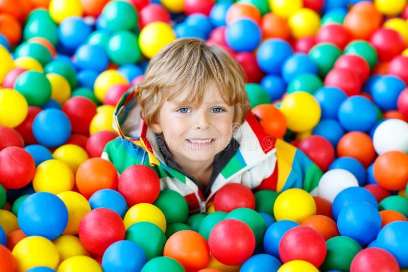 Weinig jong geitjejongen die bij kleurrijke plastic ballenspeelplaats spelen stock afbeeldingen
