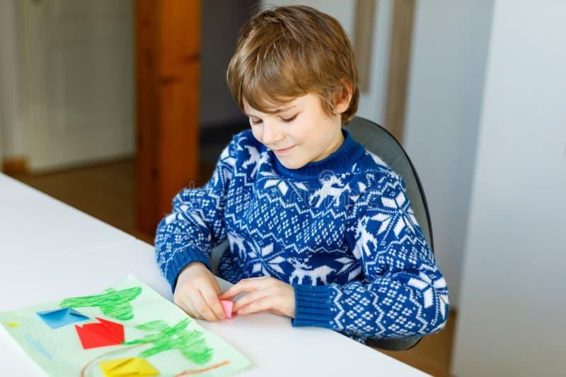 Weinig jong geitjejongen die document origamitulp maken bloeit voor een prentbriefkaar voor moeder` s dag of verjaardag Leuk kind stock foto