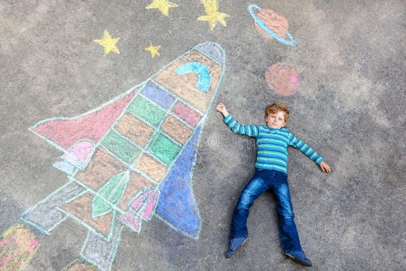 Weinig jong geitjejongen die door een beeld van het ruimteveerkrijt vliegen royalty-vrije stock fotografie