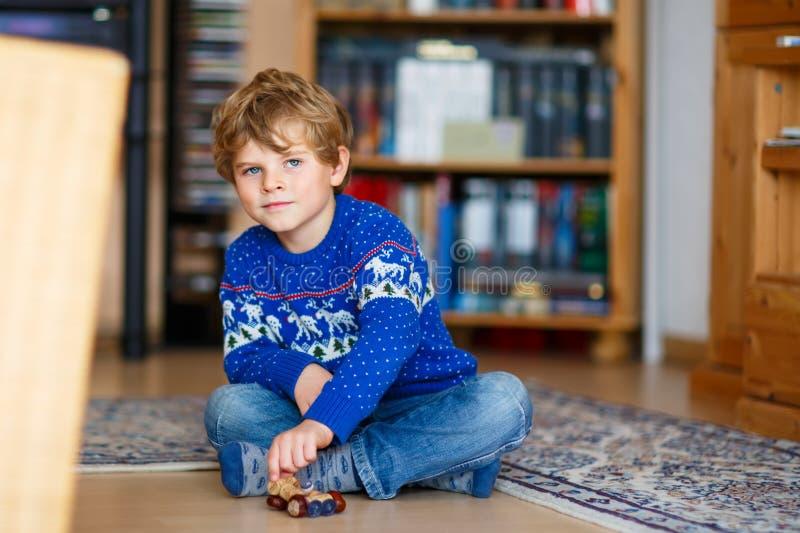 Weinig jong geitjejongen die met met de hand gemaakt kastanjestuk speelgoed binnen spelen royalty-vrije stock fotografie