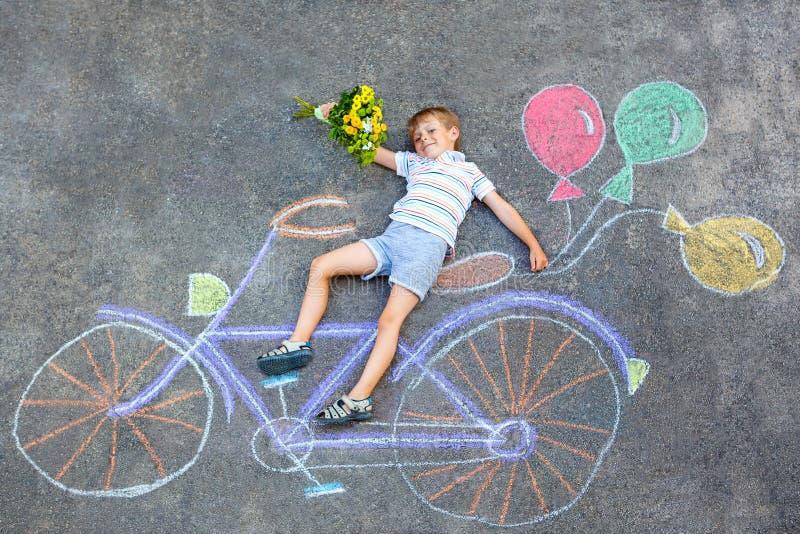 Weinig jong geitjejongen die pret met het beeld van het fietskrijt op grond hebben royalty-vrije stock afbeeldingen