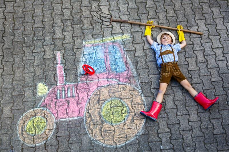 Weinig jong geitjejongen die pret met het beeld van het tractorkrijt hebben royalty-vrije stock afbeelding