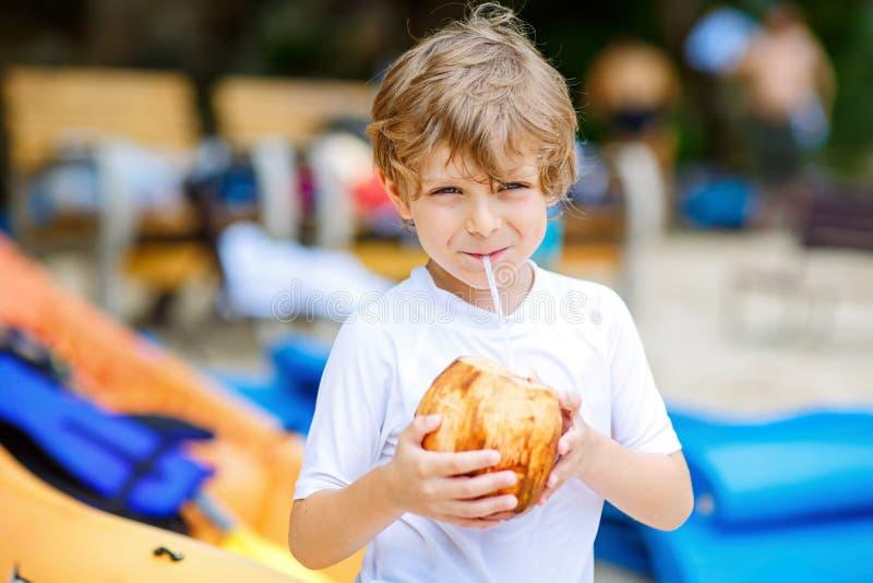 Weinig jong geitjejongen het drinken kokosnotensap op tropisch strand royalty-vrije stock afbeelding