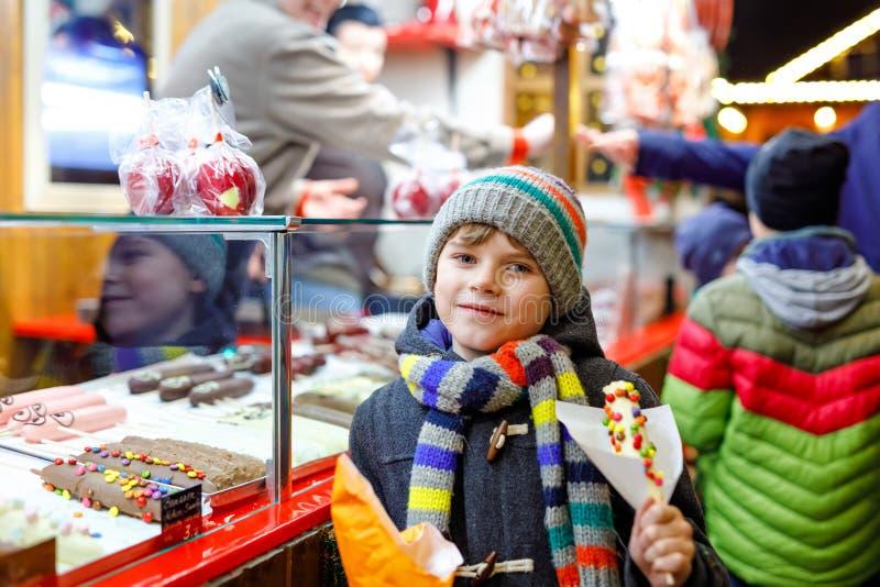 Weinig jong geitjejongen, leuk kind die die bananen eten met chocolade worden behandeld, marshmellows en kleurrijk bestrooit dich stock afbeeldingen