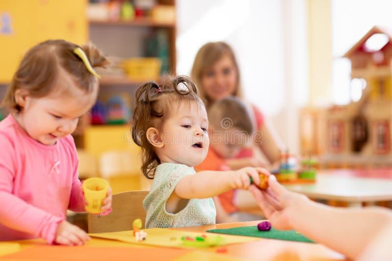 Weinig jong geitjemeisje die kleurrijke plasticine in kleuterschool leren te gebruiken stock foto's