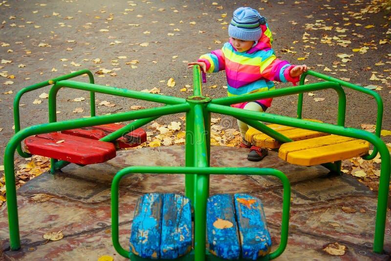 Weinig jong geitjemeisje die op carrousel spelen Het kind berijdt carrousel in kinderen` s speelplaats in de herfst stock foto's