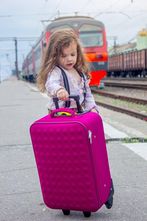 Weinig jong geitjemeisje op station met koffer met de trein op achtergrond royalty-vrije stock foto