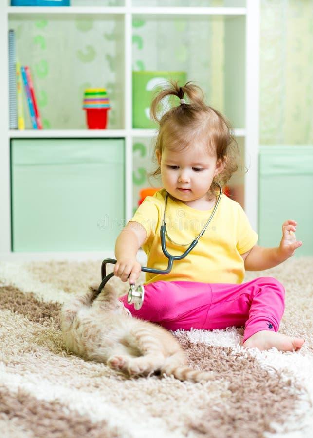 Weinig jong geitjemeisje speelt arts met katje stock foto's