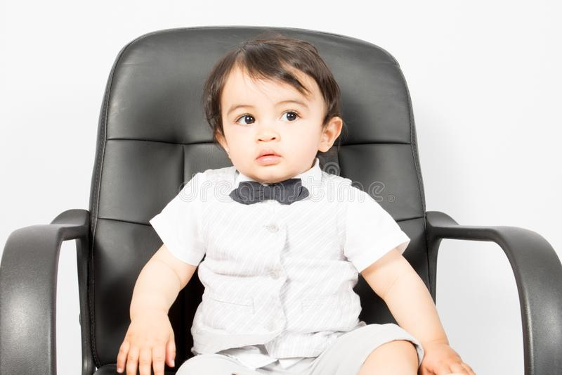Weinig jong kindjongen die een bureaustoel zitten kijken die die op witte achtergrond wordt geïsoleerd stock afbeeldingen