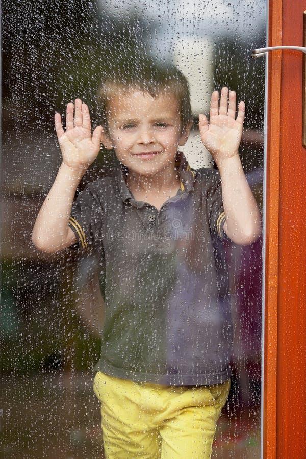 Weinig jongen achter het venster in de regen royalty-vrije stock foto's