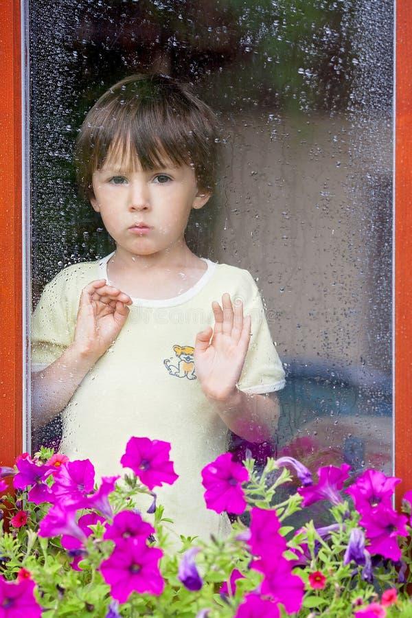Weinig jongen achter het venster in de regen royalty-vrije stock afbeelding