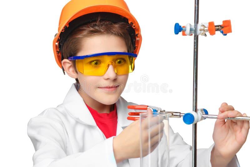 Weinig jongen als chemicus die experiment doen met stock foto