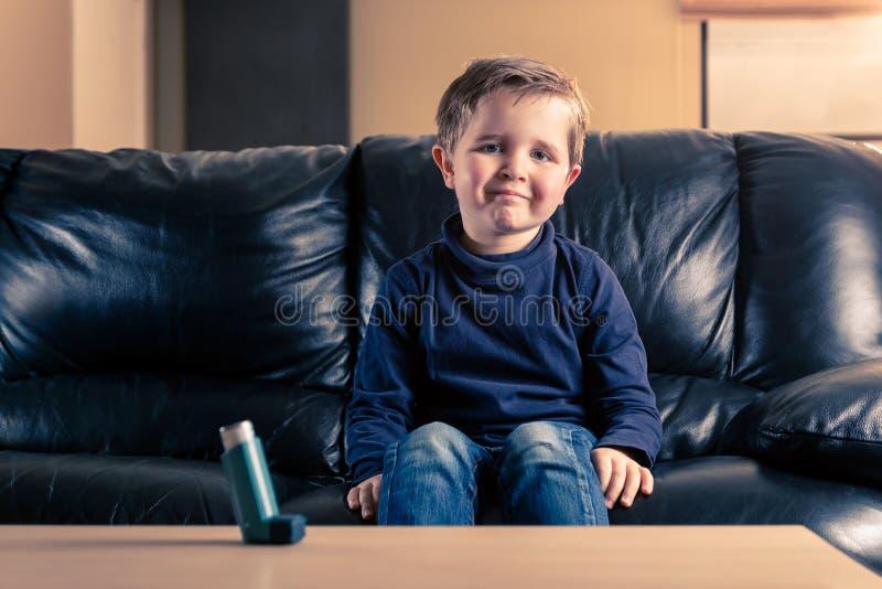 Weinig jongen in bank en met astmainhaleertoestel stock afbeelding