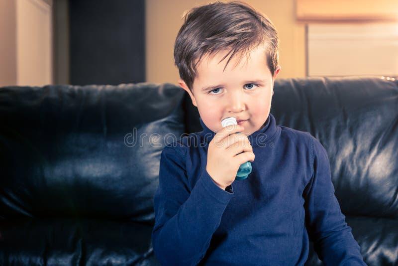 Weinig jongen in bank en met astmainhaleertoestel royalty-vrije stock afbeeldingen