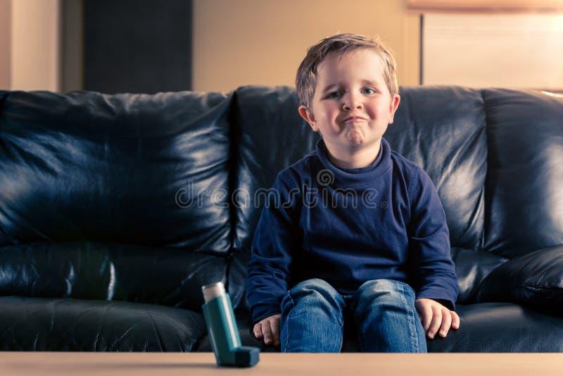 Weinig jongen in bank en met astmainhaleertoestel royalty-vrije stock fotografie