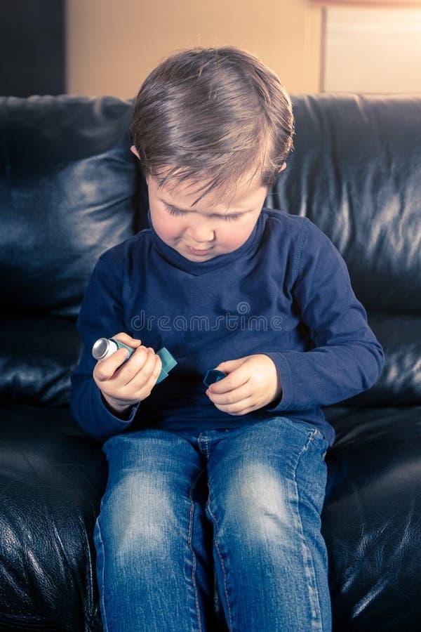 Weinig jongen in bank en met astmainhaleertoestel stock fotografie