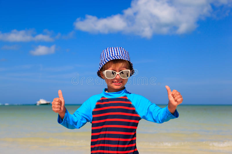 Weinig jongen beduimelt omhoog op de zomerstrand stock foto