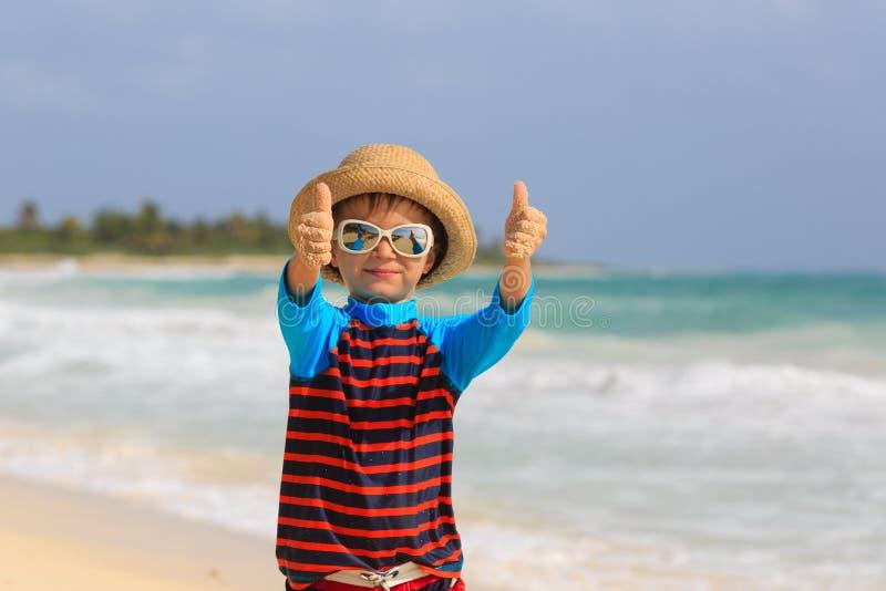 Weinig jongen beduimelt omhoog op de zomerstrand royalty-vrije stock afbeelding