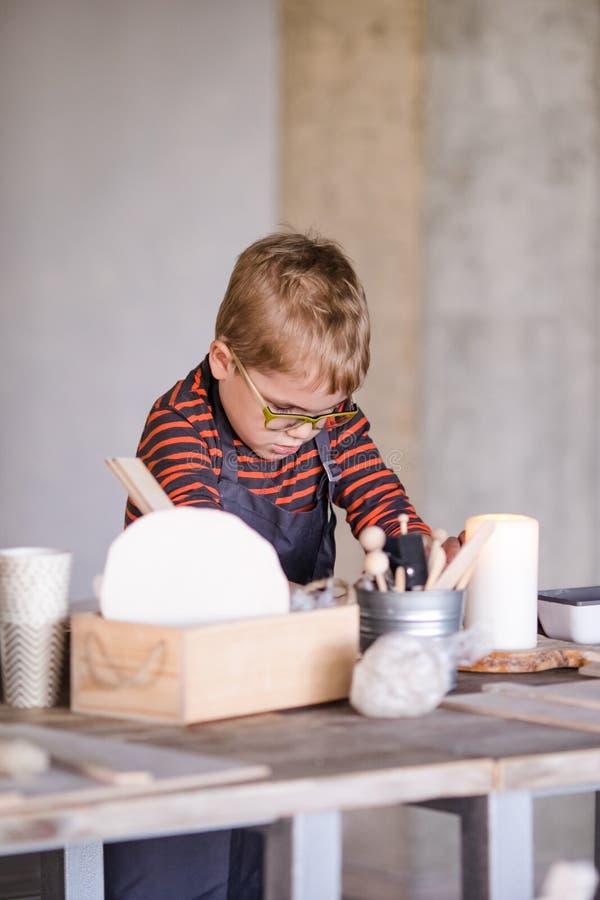 Weinig jongen beeldhouwt van klei met rente stock afbeeldingen
