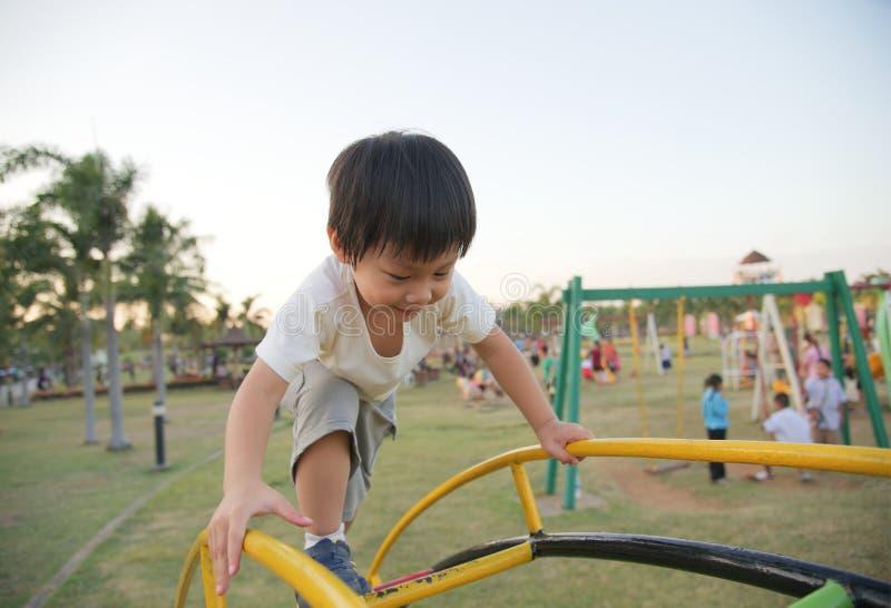Weinig jongen beklimt op de ladder op speelplaats royalty-vrije stock afbeeldingen