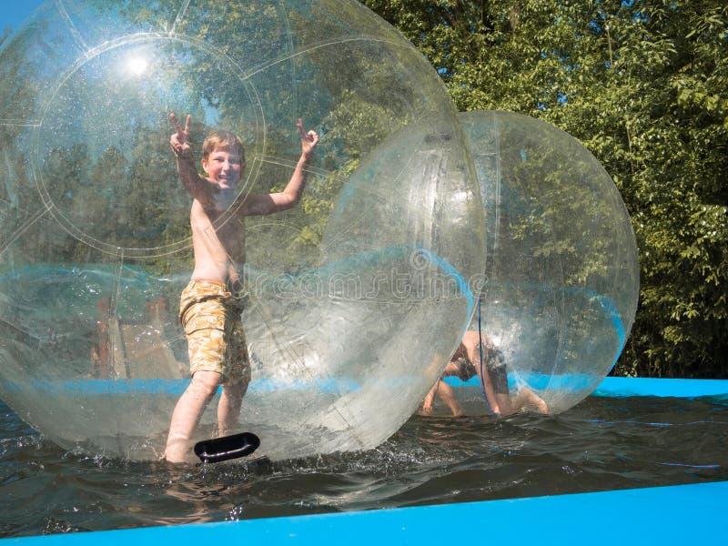 Weinig jongen bevindt zich binnen de water kom en het glimlachen royalty-vrije stock fotografie