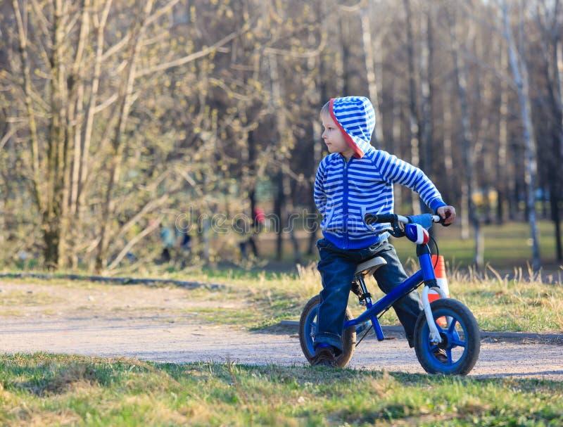 Weinig jongen bij het runnen van fiets in park stock foto's