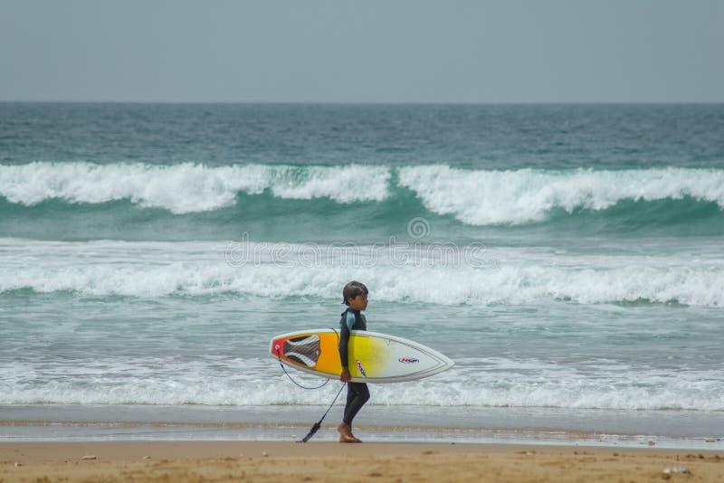 Weinig jongen bij het strand met gele surfplank op de Atlantische Oceaan met golven stock fotografie