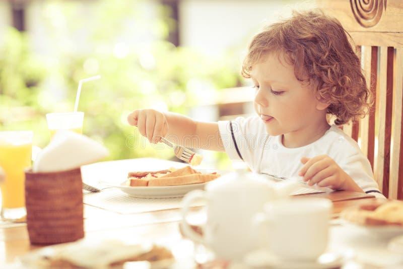 Weinig jongen bij ontbijt stock afbeelding