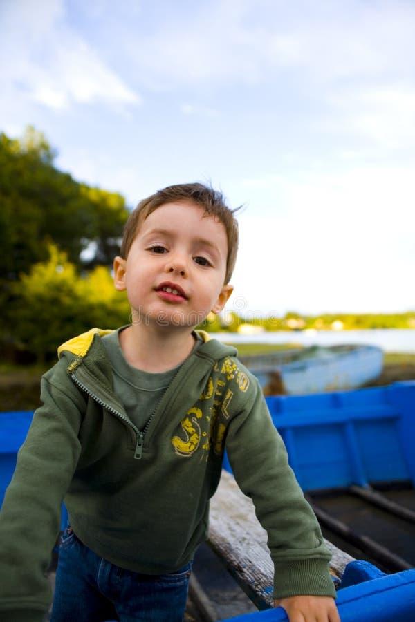 Weinig jongen in boot stock foto