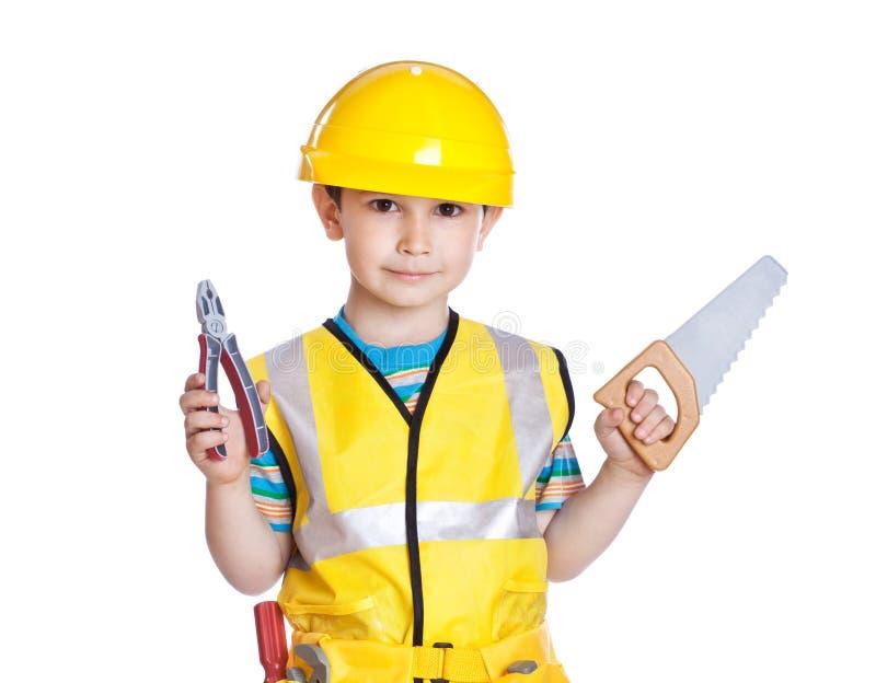 Weinig jongen in bouwer eenvormig met hulpmiddelen stock foto