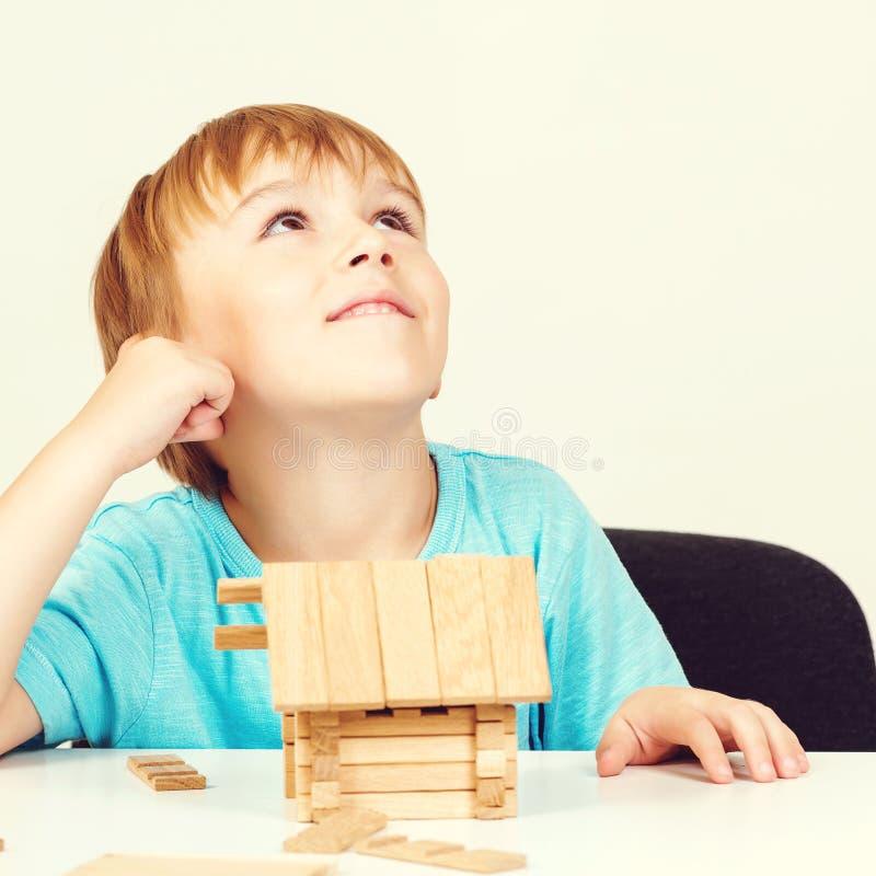 Weinig jongen bouwt huis van houten blokken Mijn huisconcept Concept droomhuis en hypotheekinvestering Weinig jongen die zoals sp stock foto's