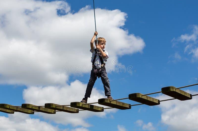 Weinig jongen bracht zwak op hoge draad met zenuwachtige blik in evenwicht tegen blauwe bewolkte hemel in Bristol, het UK royalty-vrije stock foto's