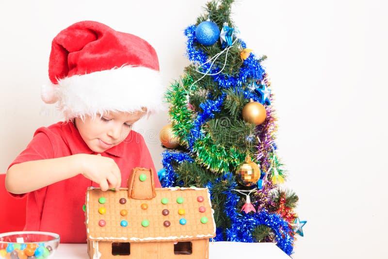 Weinig jongen in de hoed van de Kerstman de bouwpeperkoek royalty-vrije stock foto's