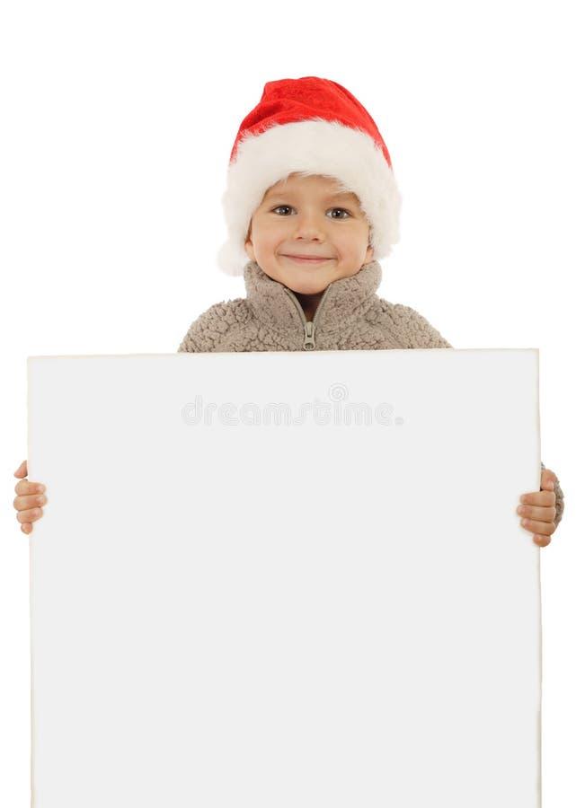 Weinig jongen in de hoed van Kerstmis met een lege banner stock afbeelding