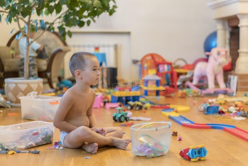 Weinig jongen in de speelkamer met speelgoed Zaal hoogtepunt van speelgoed Veel speelgoed, vele die auto's op de vloer worden opg royalty-vrije stock foto's
