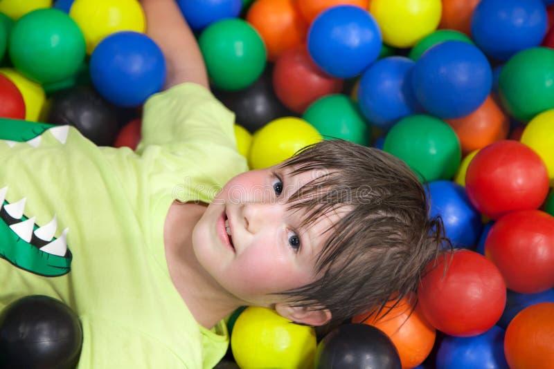 Weinig jongen in de speelplaats van de kinderen stock foto's