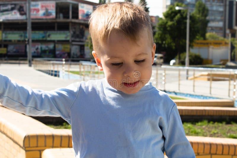 Weinig jongen in de uitdrukking van het parkgezicht royalty-vrije stock afbeelding