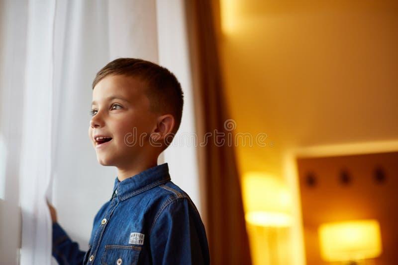 Weinig jongen dichtbij het venster binnen stock foto